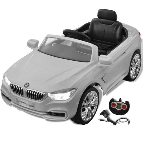 coche eléctrico BMW con el coche teledirigido blanco del niño